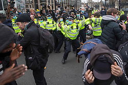 © Licensed to London News Pictures.03/04/2021. London, UK. A police officer fires pepper spray as scuffles erupt between 'Kill the Bill' protesters and police in Parliament Square, central London. The bill proposes new restrictions on protests during the Covid-19 coronavirus pandemic in England. Photo credit: Marcin Nowak/LNP