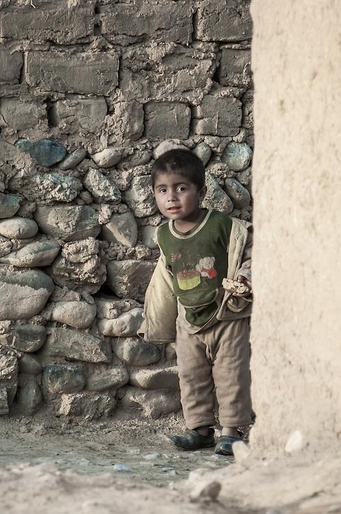 Portrait of an inquisitive village boy peering around a corner in western Tajikistan