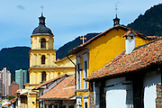 Architecture of the historic neighborhood of La Candelaria  is highlighted by the yellow tower of the Iglesia de La Candelaria and adobe houses with red bricked roofs.