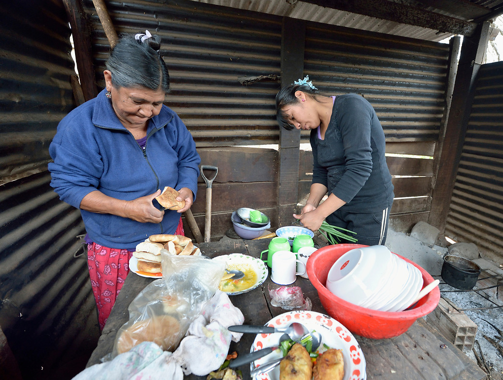 Edulia Vaquera (left) and Flora Galarza cook food in the Guarani indigenous village of Kapiguasuti, Bolivia. They and their neighbors started small gardens with assistance from Church World Service, supplementing their corn-based diet with nutritious vegetables and fruits.