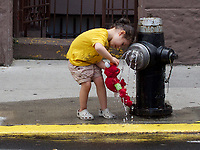 Giving Elmo a drink on a hot day on West 83rd Street in New York City