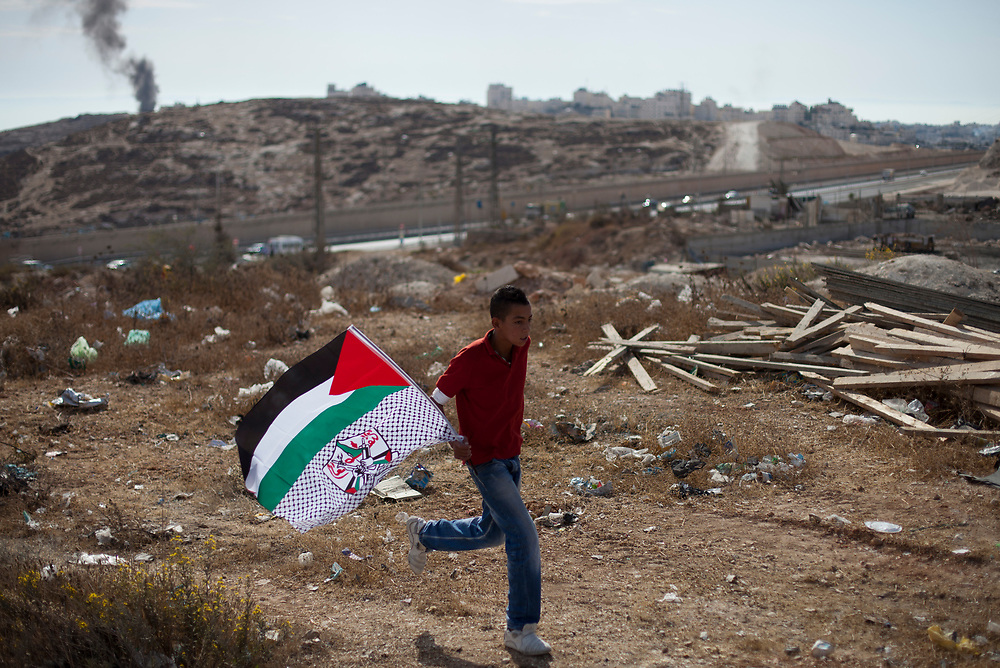 A Palestinian youth runs with a flag as Palestinians celebrate the prisoner swap deal reached between Israel and Hamas at the east Jerusalem neighborhood of Isawiyya, Israel, on October 18, 2011. Hundreds of people gathered in East Jerusalem to celebrate the return of prisoners freed under a swap deal with Israel which freed captive Israel Defense Forces soldier Gilad Shalit after five years of captivity.