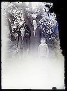 deteriorating glass plate photo of mother with with two young children