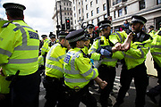 Police struggle with and arrest and remove a protester as they try to clear climate change activists from the Extinction Rebellion group at Oxford Street near to the Marble Arch camp in protest that the government is not doing enough to avoid catastrophic climate change and to demand the government take radical action to save the planet, on 24th April 2019 in London, England, United Kingdom. Extinction Rebellion is a climate change group started in 2018 and has gained a huge following of people committed to peaceful protests.