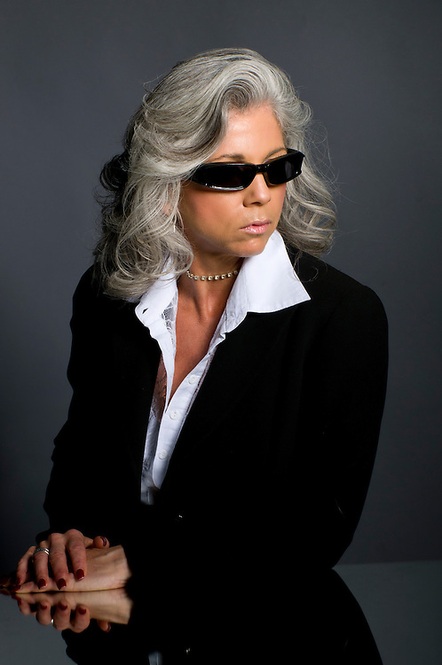Executive woman in her 50s wearing sunglasses and looking serious.