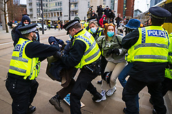"""© Licensed to London News Pictures. 27/03/2021. Manchester, UK. Police move in to remove and detain protesters who were sitting on and blocking tram tracks in St Peter's Square in Manchester City Centre . """" Kill the Bill """" and Reclaim the Streets demonstrations are held in Manchester City Centre in opposition to the Police, Crime, Sentencing and Courts Bill 2021 that is currently before Parliament and after the death of Sarah Everard in London . Photo credit: Joel Goodman/LNP"""