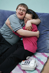 Teenage Downs Syndrome boy and girl showing affection,