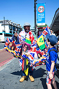 A man selling royal wedding memorabilia along Brixton Road on 19th May 2018 in South London in the United Kingdom. Located in South London on the day Prince Harry and Meghan Markle get married at Windsor Castle.