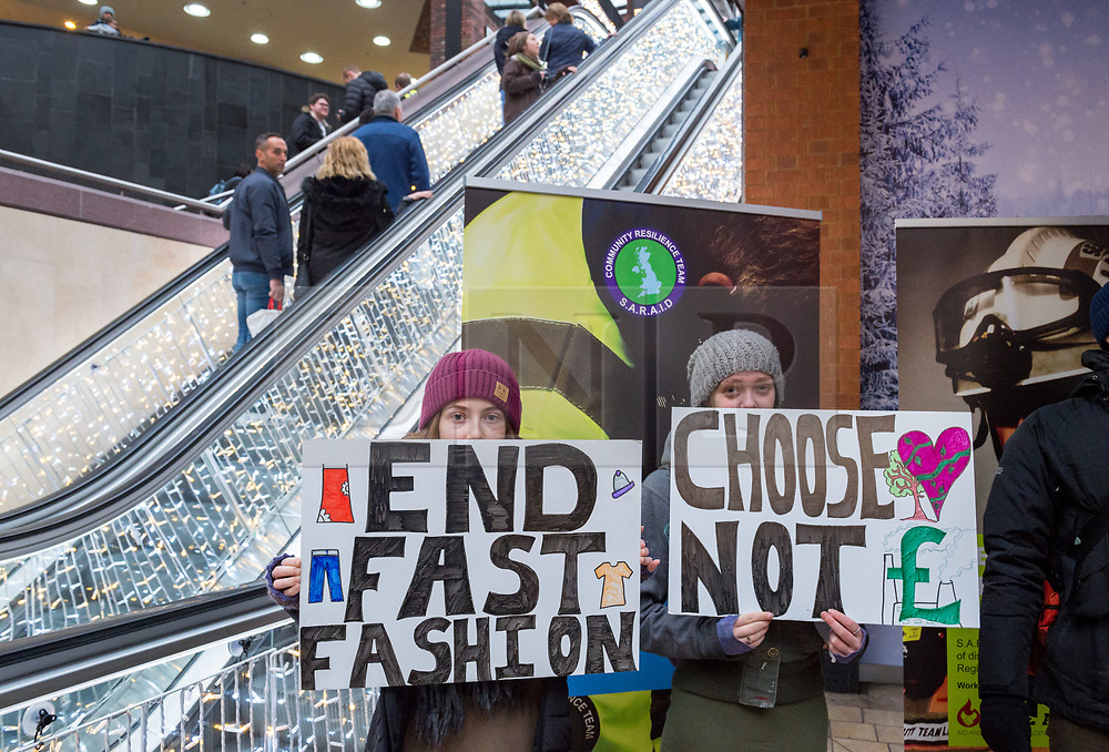 """© Licensed to London News Pictures. 15/12/2018. Bristol, UK. 'Extinction Rebellion' campaign event """"Bristol Rebellion Day"""" to draw attention to the catastrophic impact of the fast-fashion industry and Christmas on our climate and ecological systems, part of a national day of action in many towns and cities about the threat of climate change. Regional Extinction Rebellion groups are taking part non-violent action to put pressure on local councils to transform policy in line with national demands to act on climate change. Campaigners say Bristol City Council is leading the way, having declared a climate emergency in November. Campaigners gathered inside Cabot Circus on the bottom floor, with songs from the XR Choir and a die in where all activists will lay on the floor. The campaign wants to make ecocide a crime in UK law, saying the threat of climate change threatens the lives of millions of people on the planet. The campaign is organised by Rising Up. Photo credit: Simon Chapman/LNP"""