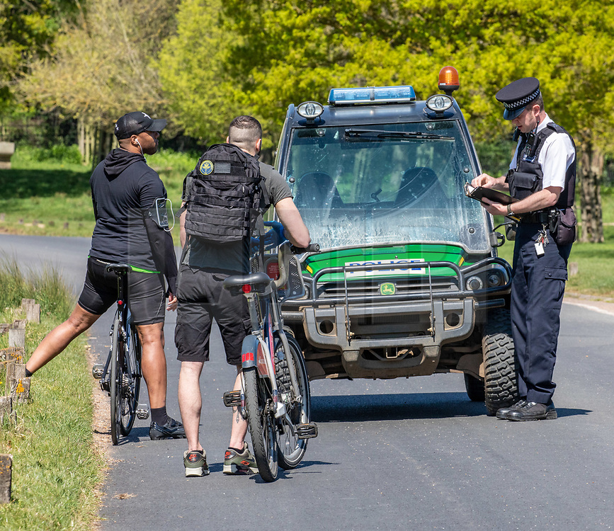 © Licensed to London News Pictures. 21/04/2020. London, UK. A Policeman stops two men on bikes where cycling and driving have been banned in the park since lockdown. Police patrol Richmond Park enforcing lockdown rules with a Police 4x4 buggy which is one of only four originally built for the Olympics and now used during the pandemic in the Royal park for its off-road capabilities. Photo credit: Alex Lentati/LNP