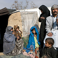 Nur Mohammed, 45 and his wife Jan Bibi and children Masouma, 2yrs,Majibin, 10, Sher Mohammed, 4, Toragha, 8 and18 year old daughter Fatima who is sick were displaced by violence and Taliban intimidation in the area around Musa Qala in Afghanistan's troubled Helmand Province  and now prepare to spend the freezing winter living in a tent in a makeshift refugee camp on the outskirts of Kabul, Afghanistan on the 13th December 2007..