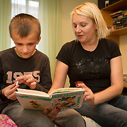 CAPTION: Dima enjoys having his mother Olga read to him, and especially appreciates the pictures in the books she chooses. However, because he is hyperactive, he is unable to focus his attention on a story for very long. He is constanly fiddling, especially with pen tops (as pictured here). NAMES MUST BE CHANGED. LOCATION: St Petersburg, Russia. INDIVIDUAL(S) PHOTOGRAPHED: Nikolay Grigoryev (son) and Olga Grigoryeva (mother).