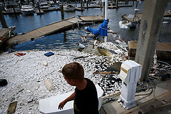 October 8, 2016 - St. Augustine Beach, Florida, U.S. - WILL VRAGOVIC       Times.Blake Shatto, 21, walks past the wreckage of a sunken sailboat, destroyed by Hurricane Matthew, at the Conch House Marina Resort in St. Augustine Beach, Fla. on Saturday, Oct. 8, 2016. (Credit Image: © Will Vragovic/Tampa Bay Times via ZUMA Wire)