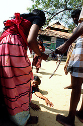 "TAMIL NADU, MARCH 1994.A woman in chains is taken by her parents to the well to be cleansed of the 'evil spirtis"". Another woman is lying on the ground lamenting."