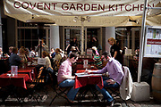 People eating outside at some of the many restaurants in the area. Covent Garden in the West End of London.