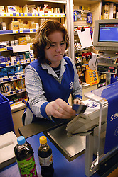 Shop assistant with learning disability taking a card payment at supermarket checkout,