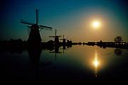 18th century windmills at full moon, Kinderdijk village, Unesco heritage.