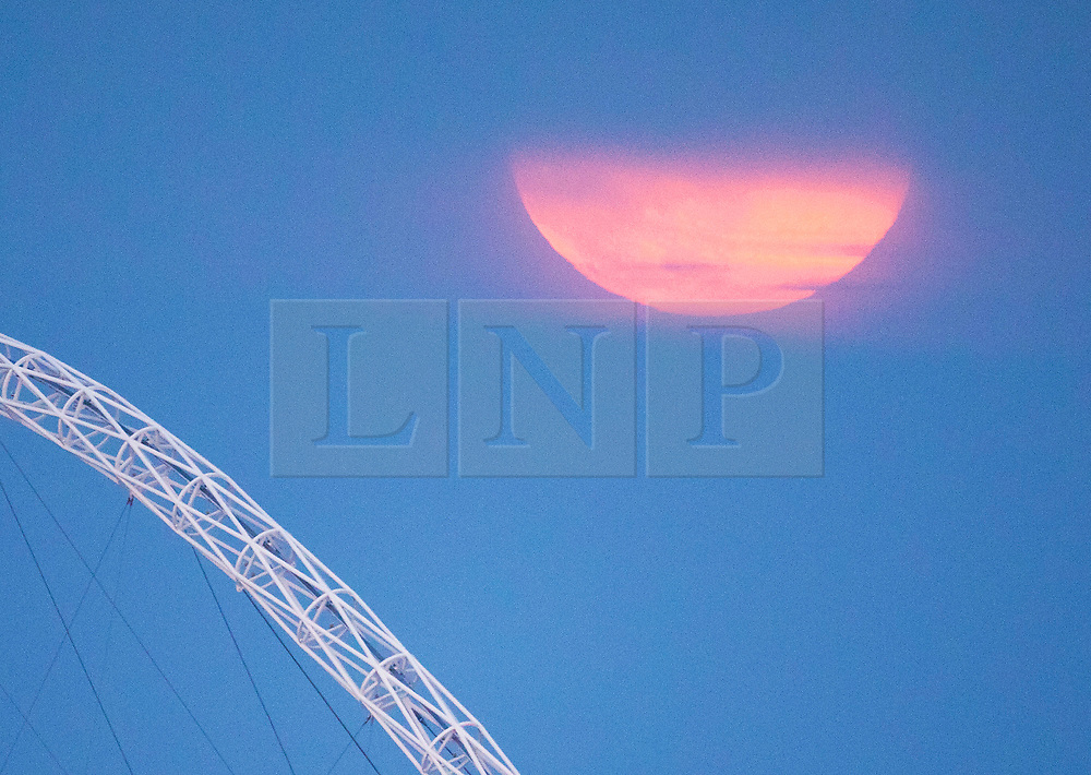 © Licensed to London News Pictures. 07/05/2020. London, UK. The Supermoon makes a brief appearance as it rises over Wembley Stadium's arch in London. Also know as the Flower Moon at this time of year a supermoon is a full or new moon that comes closest to the Earth in its elliptical orbit—resulting in a slightly larger than usual apparent size when viewed from Earth. Photo credit: Peter Macdiarmid/LNP
