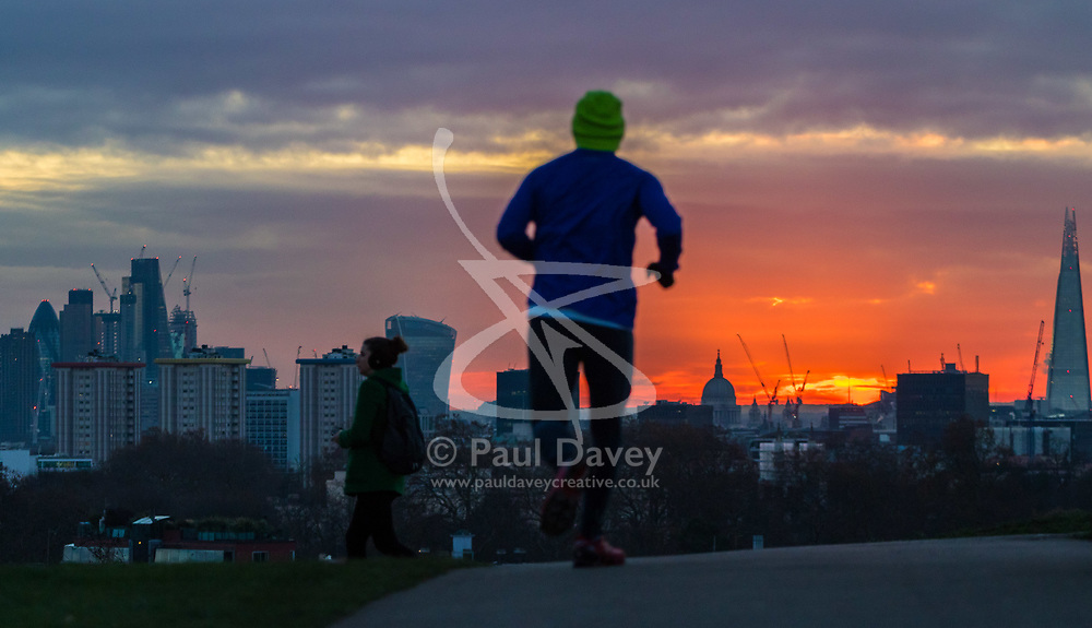 London, November 30 2017. A runner is in silhouette as the sun rises over the London skyline, seen from Primrose Hill, on a chilly London morning when overnight temperatures plunged to below freezing. © Paul Davey