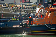 Migrants arriving into Dover docks on board an RNLI rescue boat after being rescued in the English Channel while crossing in small inflatable dinghies on the 22nd of September 2020 in Dover, Kent, United Kingdom.  About 30 men, women and children (including a baby) arrived today on two small boats they were taken off the RNLI boat by UK Boarder Force and put onto a double decker bus.