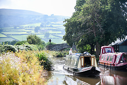 © Licensed to London News Pictures. 04/09/2021. Brecon, UK. A beautiful scene as a barge travels down the Monmouthshire and Brecon Canal in South Wales on a beautiful Saturday afternoon as people enjoy the late Summer weather across the UK. Photo credit: Robert Melen/LNP