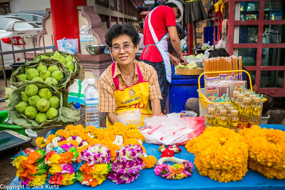 17 OCTOBER 2012 - BANGKOK, THAILAND:    A flower garland vendor in front of a Chinese shrine during the Vegetarian Festival in Bangkok. People make extra offerings during the Vegetarian Festival and garland vendors set up in front of most of the temples and Chinese shrines. The Vegetarian Festival is celebrated throughout Thailand. It is the Thai version of the The Nine Emperor Gods Festival, a nine-day Taoist celebration celebrated in the 9th lunar month of the Chinese calendar. For nine days, those who are participating in the festival dress all in white and abstain from eating meat, poultry, seafood, and dairy products. Vendors and proprietors of restaurants indicate that vegetarian food is for sale at their establishments by putting a yellow flag out with Thai characters for meatless written on it in red.    PHOTO BY JACK KURTZ
