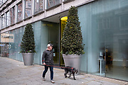 Man walks his dog past the entrance of a hotel with large scale sculpted trees outside on 15th April 2021 in London, United Kingdom.