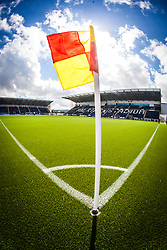 Sunlight catches behind the corner flag at The Falkirk Stadium, with the new pitch work for the Scottish Championship game v Morton. The woven GreenFields MX synthetic turf and the surface has been specifically designed for football with 50mm tufts compared with the longer 65mm which has been used for mixed football and rugby uses.  It is fully FFA two star compliant and conforms to rules laid out by the SPL and SFL.<br /> ©Michael Schofield.