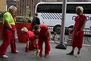 Men on a stag party, dressed up as blonde kung fu fighters in red martial arts outfits fighting for fun on the street. UK.