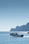 View of sea and mountain, motorboat making waves, Port de Girolata, Scandola Nature Reserve, Corsica, France