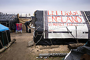 """Calais, Januari 2015. Human rights watch reports about the conditions thousands of stranded refugees have to deal with in Calais, on their way to the UK. In camps or 'jungles', several thousand asylum seekers and migrants, people from Syria, Iraq, Eritrea, Ethiopia, Sudan, Pakistan and Afghanistan are living in makeshift camps or in the streets in Calais. Some said that their treatment by police, a lack of housing for asylum seekers, and delays in the French asylum system had deterred them from seeking asylum in France. Exterior at Tioxide jungle with a slogan used during a manifestation """"let's go England, we respect France"""""""