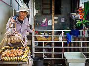 15 AUGUST 2017 - BANGKOK, THAILAND: A food vendor walks along a narrow foot path next to a home in the Wat Thewarat Kunchorn community. The community is one of the 14 riverside communities that will be torn down to make way for a riverfront promenade. Construction of the 14 kilometer long promenade will start in late 2017.      PHOTO BY JACK KURTZ