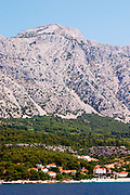 Mountain top of the Mount Sveti Ilija, with white rock formations. At sea level the Orebic village. Peljesac Peninsula. Orebic town. Peljesac peninsula. Dalmatian Coast, Croatia, Europe.
