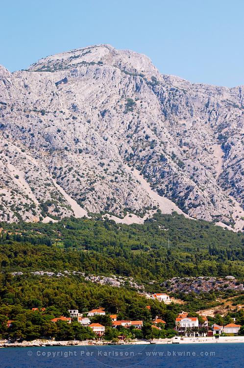 Mountain top of the Mount Sveti Ilija, with white rock formations. At sea level the Orebic village. Peljesac Peninsula. Orebic town. Peljesac peninsula. Dalmatian Coast, Croatia, Europe.