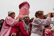 Transvestites from the Elizabeth Club dance and enjoy carrying a mikoshi or portable shrine featuring a large pink phallus during the Kanamara matsuri, Kawasaki Daishi, Japan April 5th 2009