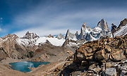 """Mount Fitz Roy (3405 m or 11,171 ft elevation) rises above Laguna de Los Tres in Los Glaciares National Park, Santa Cruz Province, Argentina, Patagonia, South America. The trail called Sendero Fitz Roy leads from El Chalten to Laguna de Los Tres (20 km round trip with 1100 meters gain). Monte Fitz Roy is also known as Cerro Chaltén, Cerro Fitz Roy, or Mount Fitz Roy. The first Europeans recorded as seeing Cerro Fitz Roy were the Spanish explorer Antonio de Viedma and his companions, who in 1783 reached the shores of Viedma Lake. In 1877, Argentine explorer Francisco Moreno saw the mountain and named it Fitz Roy in honour of Robert FitzRoy who, as captain of HMS Beagle, had travelled up the Santa Cruz River in 1834 and charted large parts of the Patagonian coast. Mt Fitz Roy was first climbed in 1952. Cerro is a Spanish word meaning hill, while Chaltén comes from a Tehuelche word meaning """"smoking mountain"""", due to clouds that usually form around the peak.  Los Glaciares National Park and Reserve are honored on UNESCO's World Heritage List. This image was stitched from multiple overlapping photos."""