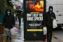 © Licensed to London News Pictures. 20/01/2021. London, UK. Shoppers wearing a protective face coverings walk past the government's 'Don't Help The Virus Spread' publicity campaign poster in north London, after the mutated variant of the SARS-Cov-2 virus continues to spread around the country. On Tuesday 19 January, 1,610 people died in the UK within 28 days of a positive Covid-19 test. This is the biggest figure reported in a single day in the UK since the pandemic began last year. According to government figures over 4.2 million people have now received the first dose of a vaccine. Photo credit: Dinendra Haria/LNP