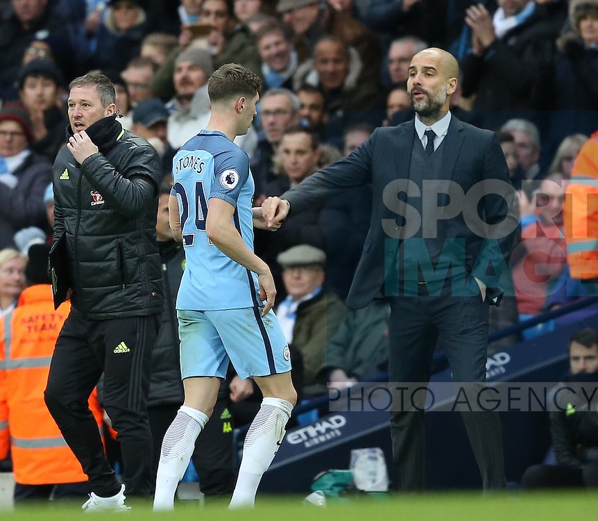 John Stones of Manchester City is ignored by Josep Guardiola manager of Manchester City as he brings him off during the Premier League match at the Etihad Stadium, Manchester. Picture date: December 3rd, 2016. Pic Simon Bellis/Sportimage