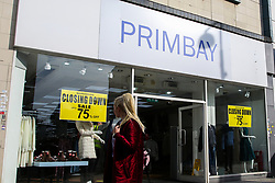 © Licensed to London News Pictures. 19/10/2020. London, UK. A woman in north London walks past 'CLOSING DOWN SALE' sign in a shop window which is closing due to coronavirus crisis. According to the figures, revealed by the Local Data Company and advisory firm PricewaterhouseCoopers (PwC), a total of 11,120 shops on UK high streets closed in the first half of this year due to the coronavirus lockdown.  Photo credit: Dinendra Haria/LNP