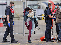 © Licensed to London News Pictures. 25/07/2021. Dover, UK. A young migrant is carried ashore by another surrounded by Border Force officers at Dover Harbour in Kent after crossing the English Channel. Hundreds of migrants have made the crossing in the calm weather this week. Photo credit: Stuart Brock/LNP
