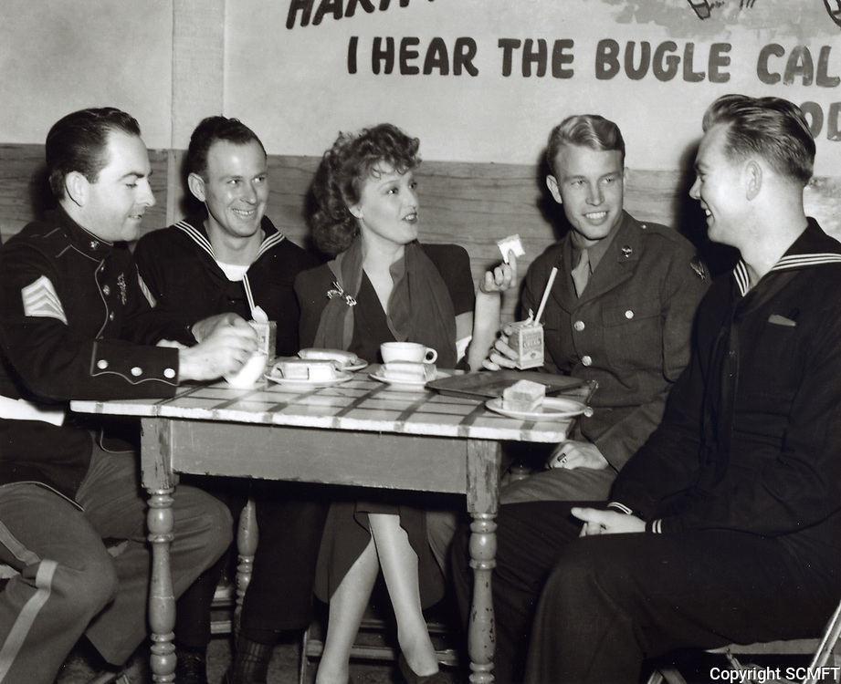 1944 Jeanette MacDonald chats with a group of servicemen at the Hollywood Canteen