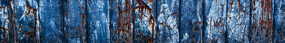 The dated blue, metal flashings of a dilapidated building have advanced areas of rust that provides a most surrealistic appearance, near Hastings Street, Vancouver British Columbia, Canada.<br /> <br /> The blue paint is very faded and is also peeling. The rust runs mostly in long, thin, vertical lines.