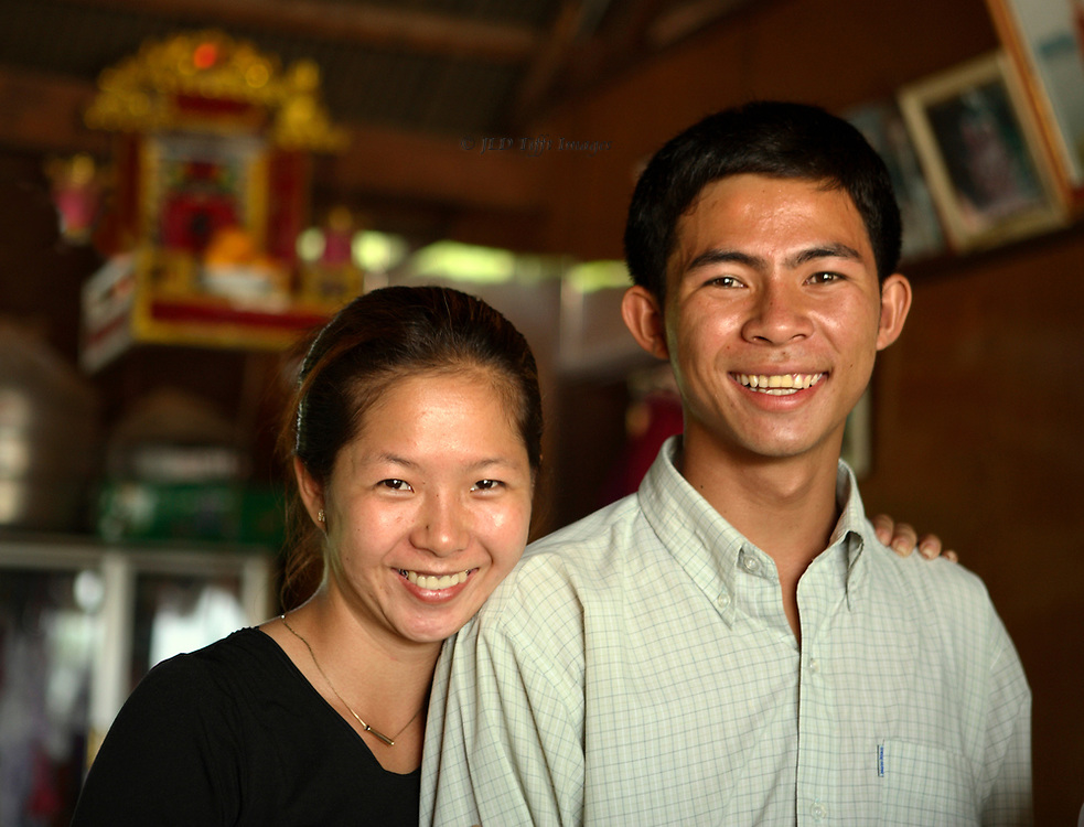 Head and shoulders double portrait of a Cambodian brother and sister, both smiling.