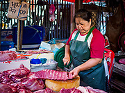 20 JUNE 2018 - BANGKOK, THAILAND: A butcher cuts up pork ribs at Makkasan Market, a small local market in central Bangkok. Officials in Thailand are wrestling with Thais use of plastic bags. The issue became a very public one in early June when a whale in Thai waters died after ingesting 18 pounds of plastic. In a recent report, Ocean Conservancy claimed that Thailand, China, Indonesia, the Philippines, and Vietnam were responsible for as much as 60 percent of the plastic waste in the world's oceans.     PHOTO BY JACK KURTZ