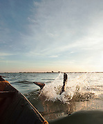 A sand diver jumps into the water of the Niger River, early in the morning at Segou, Mali. People dive to the bottom of the river, filling buckets with sand to be used in construction all over the country. Many people die each year doing this dangerous job