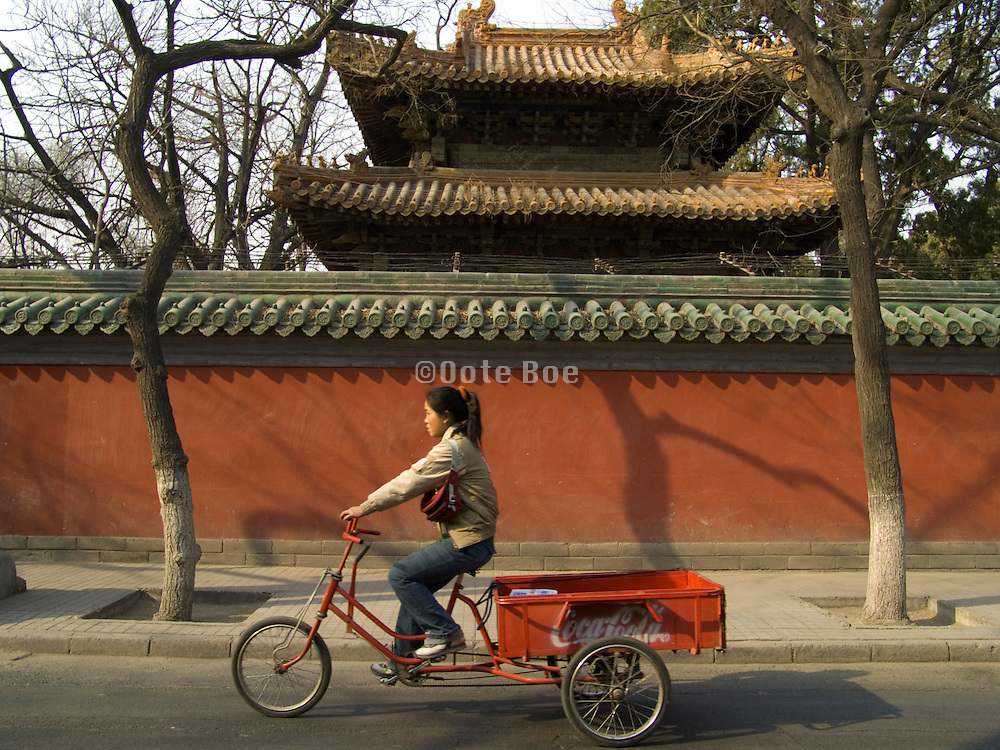 young girl riding a bicycle cart with the Coca Cola logo painted on the side of the cart China Beijing