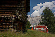 Typical old Alpine timber hut and hay collecting vehicle in the Pralongià above San Cassiano-St. Kassian in the Dolomites, south Tyrol, northern Italy. In winter, the Pralongià meadows are the heart of Alta Badia's skiing area.