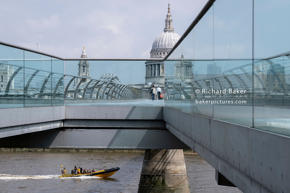 With the dome of St Paul's cathedral in the distance, a Thames Rib Experience boat speeds on the river Thames and beneath the Millennium Bridge, on 24th June 2021, in London, England. London's newest river crossing for 100-plus years coincided with the Millennium. It was hurriedly finished and opened to the public on 10 June 2000 when an estimated 100,000 people crossed it to discover the structure oscillated so much that it was forced to close 2 days later. Over the next 18 months designers added dampeners to stop its wobble but it already symbolised what was embarrassing and failing in British pride. Now the British Standard code of bridge loading has been updated to cover the swaying phenomenon, referred to as 'Synchronous Lateral Excitation'. (Photo by Richard Baker / In Pictures via Getty Images) CREDIT RICHARD BAKER.