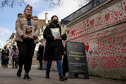 "© Licensed to London News Pictures. 08/04/2021. London, UK. Abbie Weetman (left) carries a photograph of her grandad Clemence David Abbott who died of COVID-19 as she ""walks the wall"" to mark the completion of the approximately 150,000 hearts painted onto the National Covid Memorial Wall on the Thames Embankment opposite the Houses of Parliament. Members of the public are invited to walk the length of the memorial, and campaigners are asking Prime Minister Boris Johnson to make the memorial permanent. Photo credit: Rob Pinney/LNP"