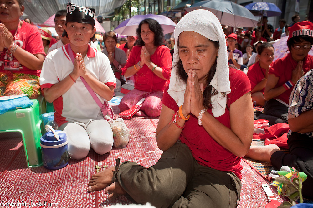 """10 MAY 2010 - BANGKOK, THAILAND: Thais pray during a memorial service for Red Shirts killed in political violence on April 10. The Red Shirts held a special memorial service at their main protest site in Ratchaprasong Intersection Monday with Buddhist monks leading chants to mark the one month anniversary of the street violence on April 10 that left 25 dead and more than 800 injured. Thai media is reporting that Prime Minister Abhisit Vejjajiva has given the Red Shirts has given the Red Shirts until the end of today to either accept his """"Road Map for Reconciliation"""" and end the protest or face unspecified consequences widely thought to include a military crackdown.   Photo by Jack Kurtz / ZUMA Press"""